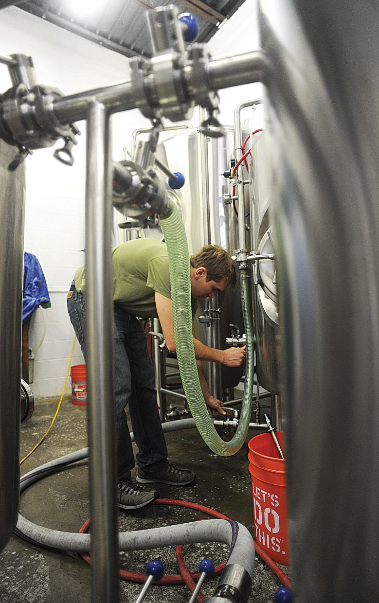 Wyatt Peterson sanitizes a fermenting tank at Storm Peak Brewery in Steamboat Springs. Wyatt may be one of the owners, but said keeping things clean is one of the biggest, and most time consuming jobs at the brewery. He jokes that he is a part time brewer, and a full time janitor.