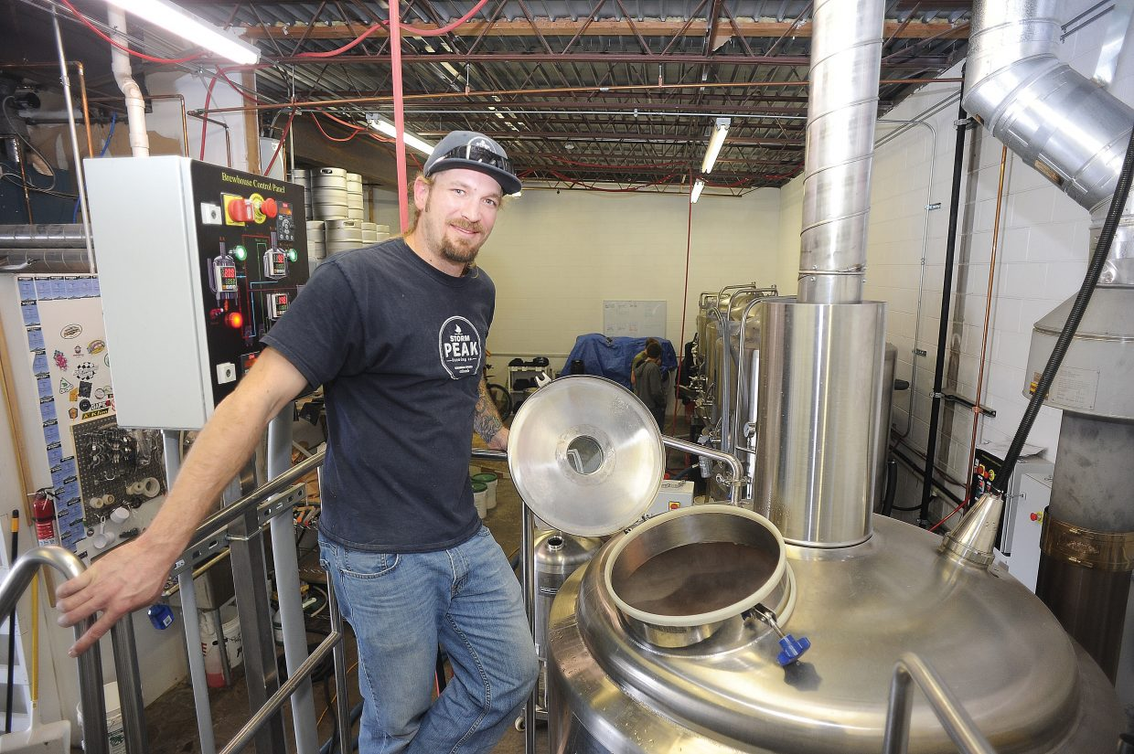 Tyler Peterson waits by the brewing kettle at Storm Peak Brewing for the next step in the process.