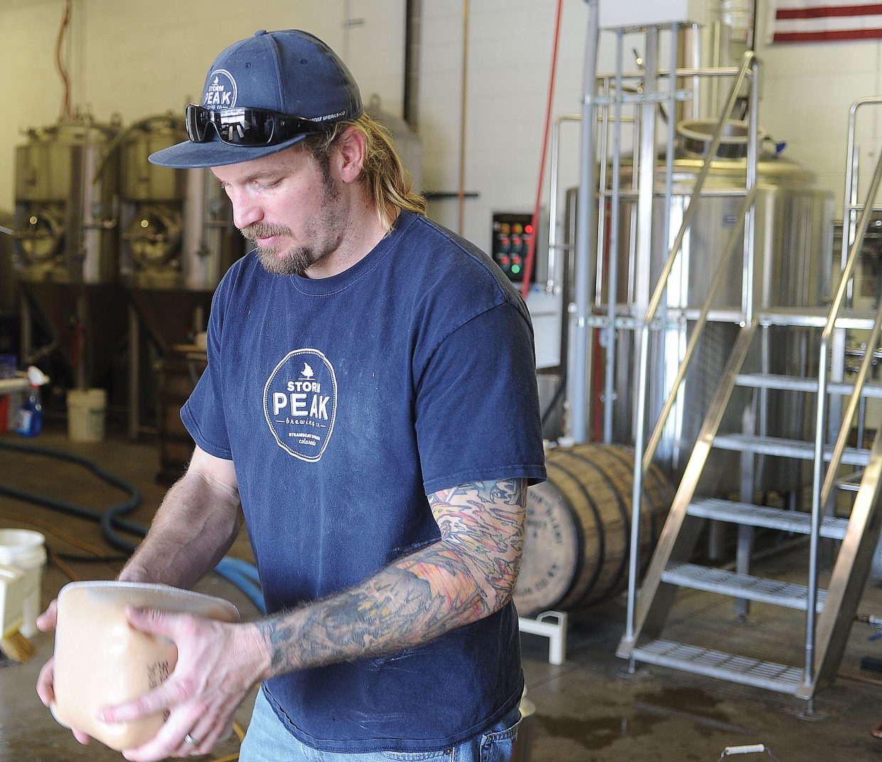 Tyler Patterson, who owns Storm Peak Brewery with his brothers and father, shakes up the yeast he will be using while brewing the Funky Touch pale ale.