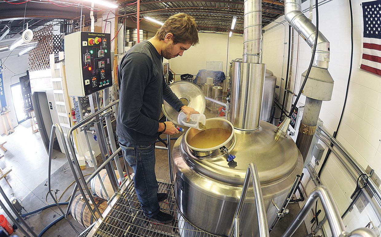 Zach Peterson adds hops to the mix while brewing Funky Touch Belgian Pale Ale at Storm Peak Brewery in Steamboat Springs.