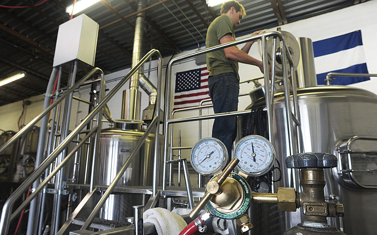 Gages fill the foreground as Wyatt Peterson checks out one of the brewing tanks at Storm Peak Brewery in Steamboat Springs.