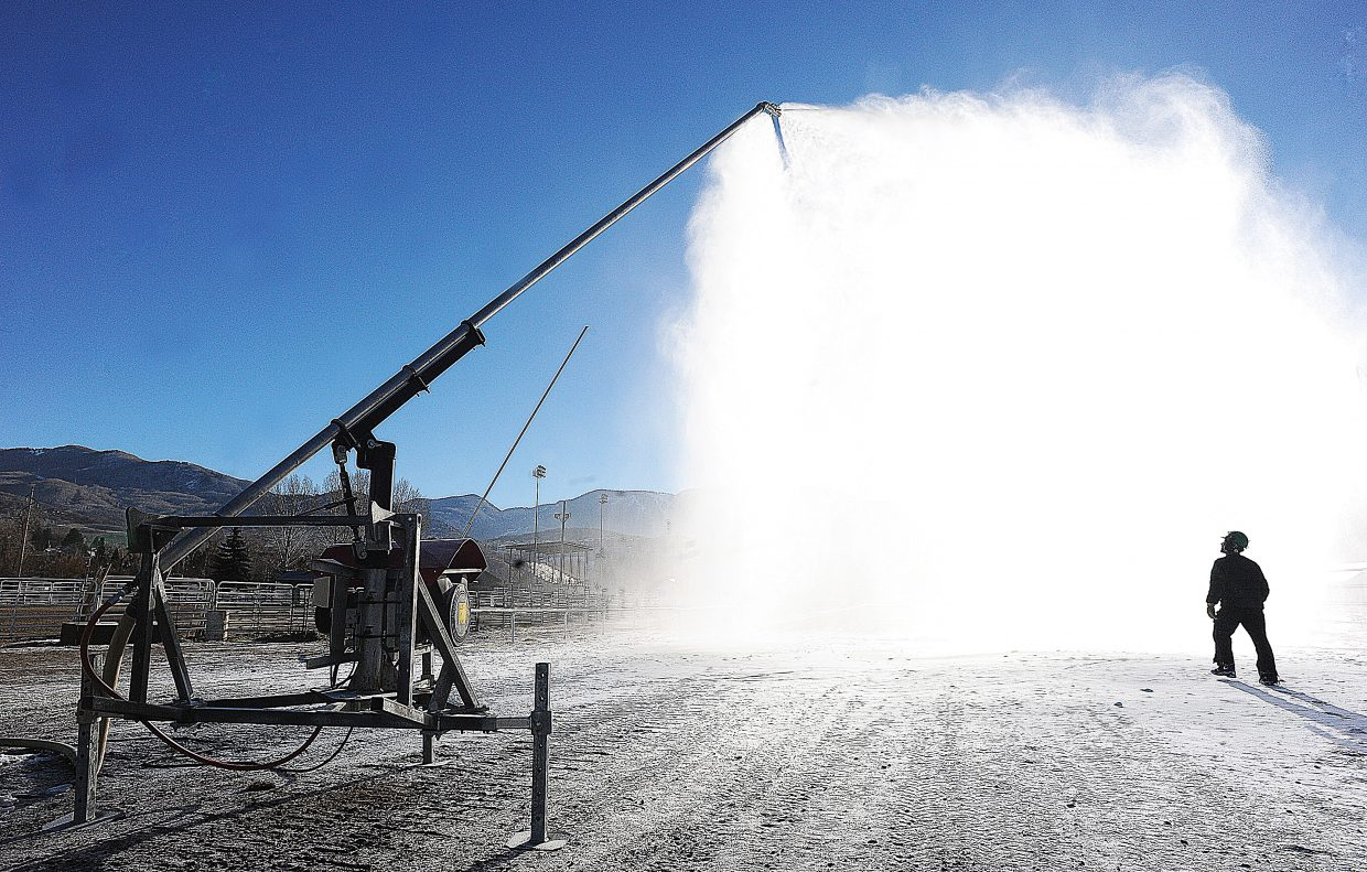 Snowmaker Scott Larson is silhouetted against a plume of man made snow as he checks one of the smaller snow-making guns at the base of Howelsen Hill.