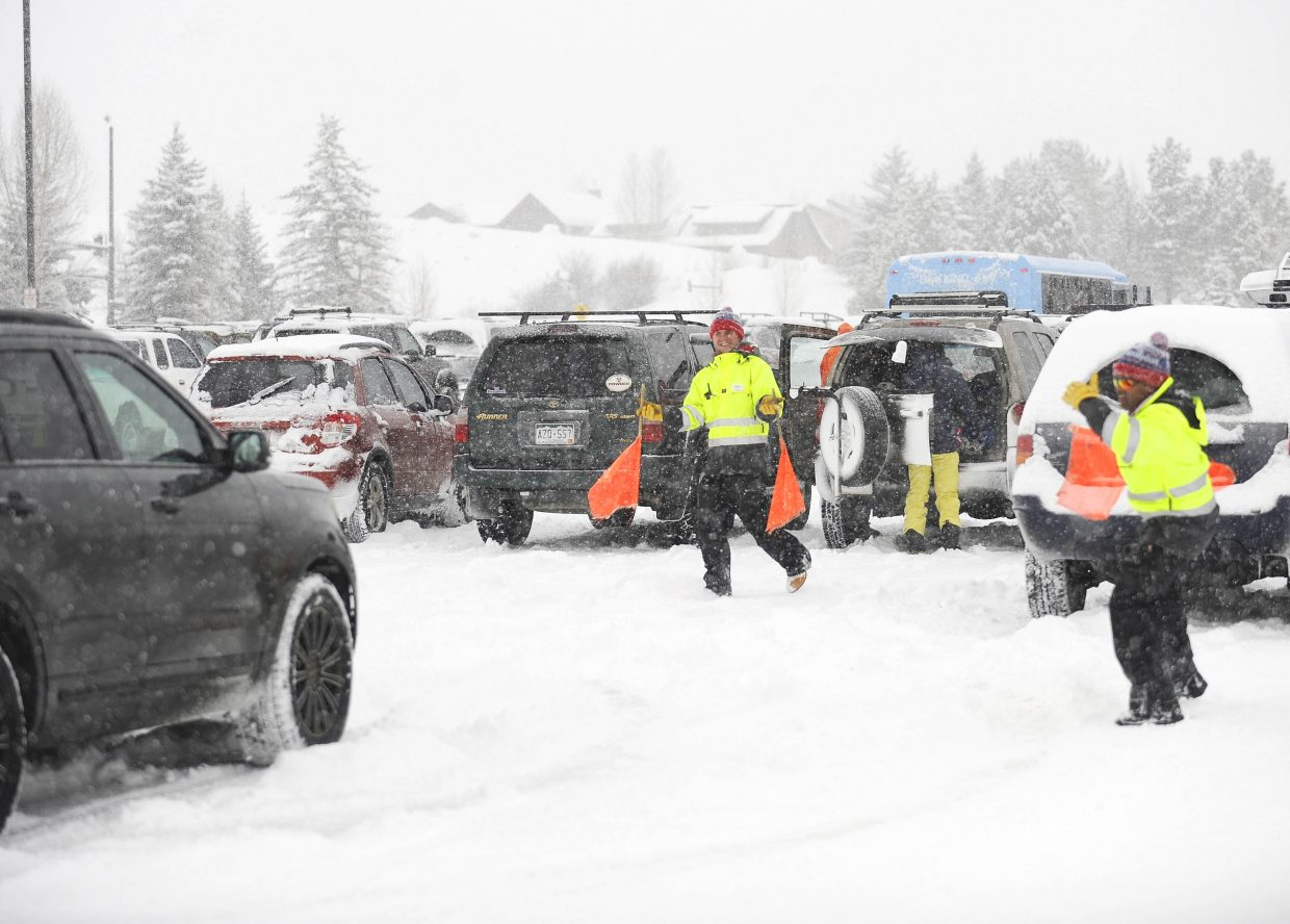 Steamboat Ski and Resort Corp. employees Dexter Saulisbury, right, and Trevor Dean direct cars Wednesday at the Meadows parking lot. The lot was busy as fresh snow fell in Steamboat Springs.