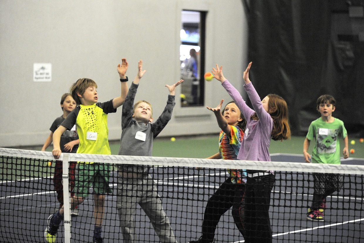 Local youth go after a ball while playing a game Wednesday during a free youth beginner tennis camp at The Tennis Center at Steamboat Springs.