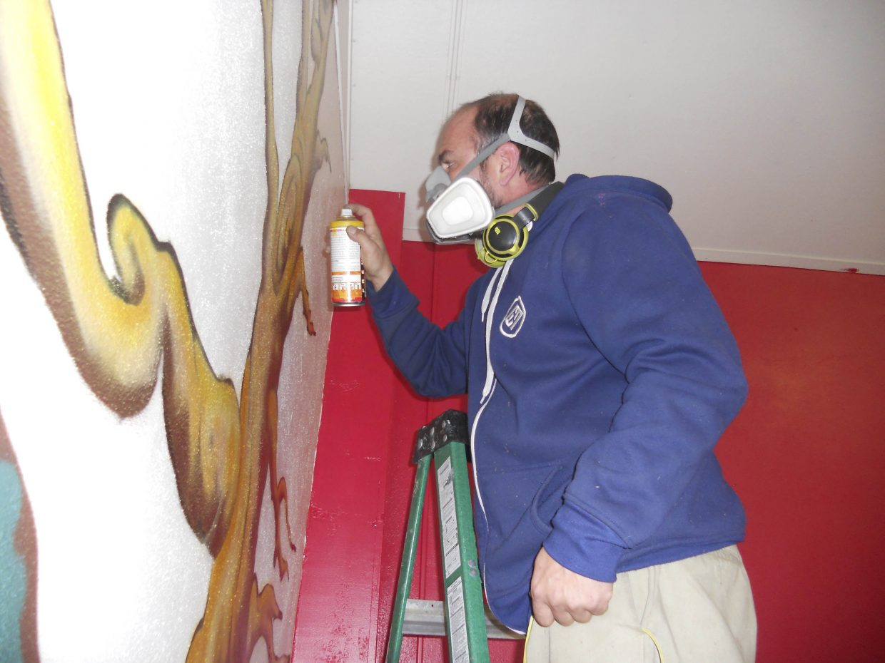 Justin Hayes paints a mural on a wall at the H Town Underground gym.