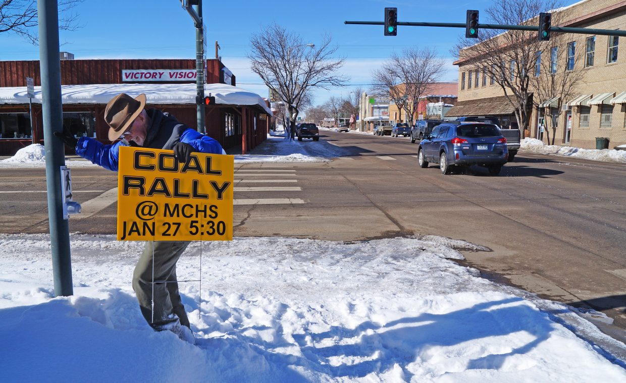 Terry Carwile, community liason for Tri-State Generation and Transmission Association, plants a sign at Yampa Avenue and Victory Way to let the community know about the upcoming coal meeting at 5:30 p.m. Wednesday.