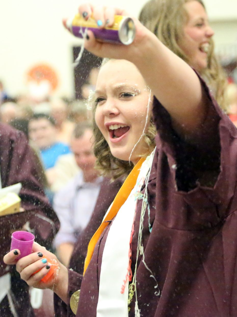 Soroco High School 2015 class salutatorian Brooke Green sprays her senior classmates with silly string following the closing remarks of their graduation on Saturday, May 23, 2015, in Oak Creek.