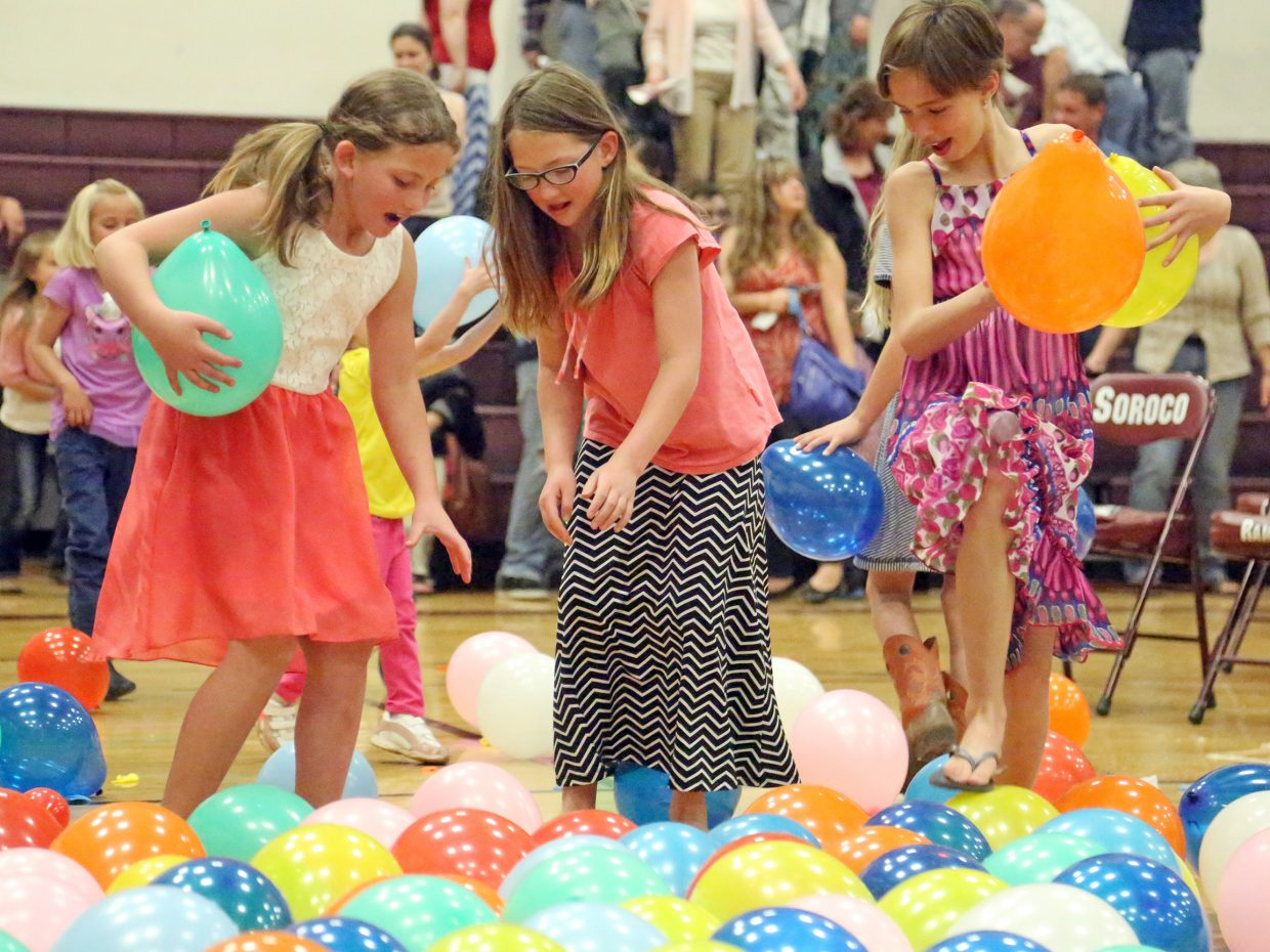Children play with balloons following the Soroco High School graduation on Saturday, May 23, 2015, in Oak Creek.