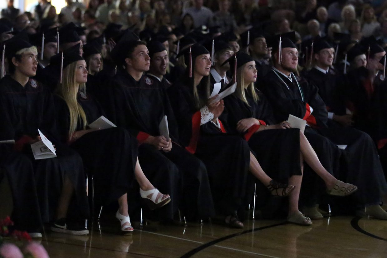 Students watch the senior slide show during the 2015 Steamboat Springs High School class graduation on Saturday, June 6, in the school gymnasium.