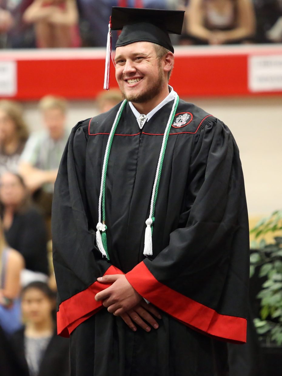Logan Bankard smiles as he walks across the stage during the 2015 Steamboat Springs High School class graduation on Saturday, June 6, in the school gymnasium.