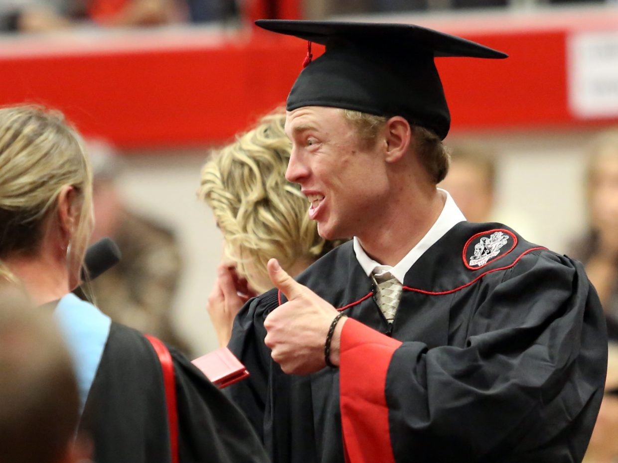 Jesse Pugh signals to the crowd during the 2015 Steamboat Springs High School class graduation on Saturday, June 6, in the school gymnasium.
