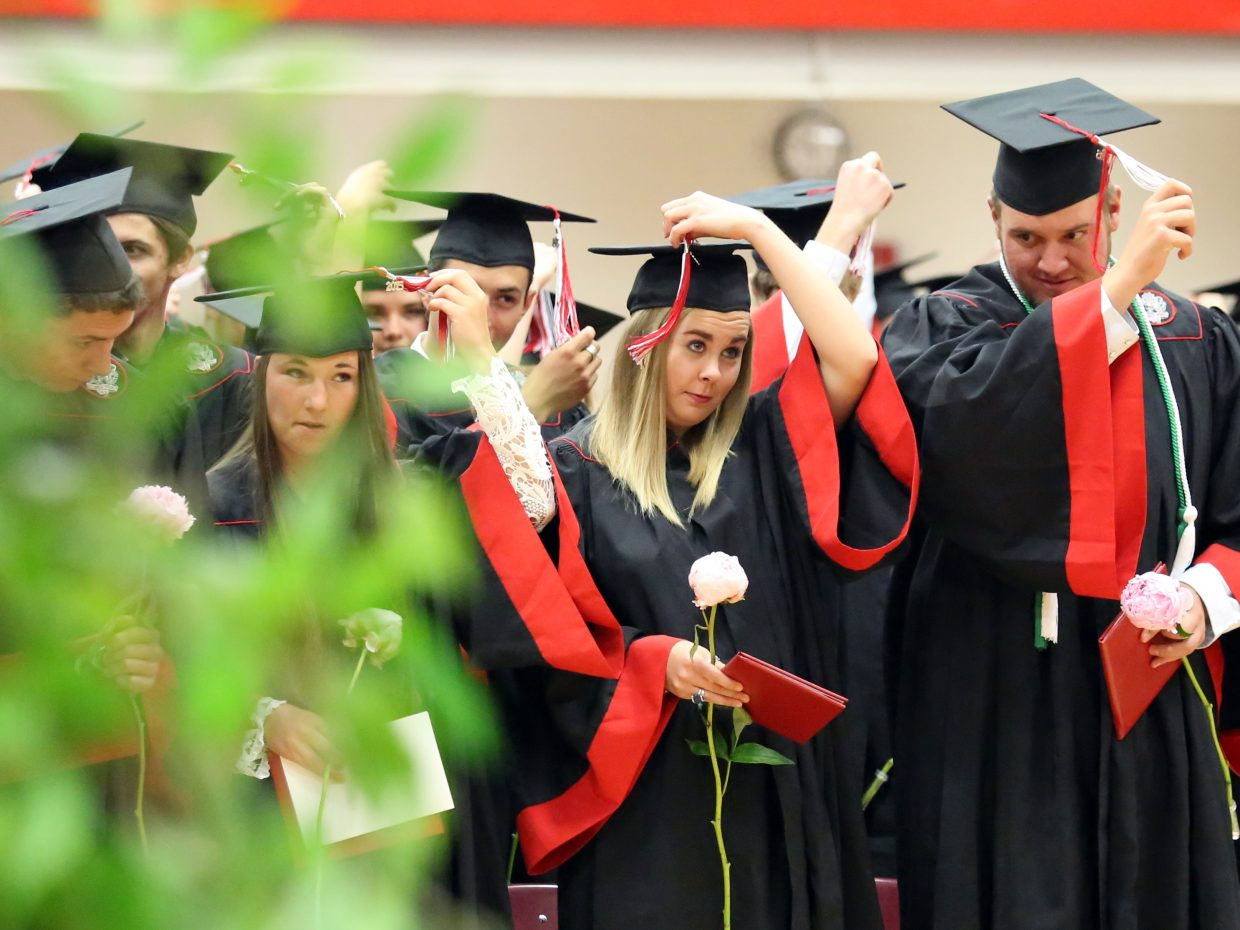 Students move their tassels from one side to the other to signify their status as graduates during the 2015 Steamboat Springs High School class graduation on Saturday, June 6, in the school gymnasium.