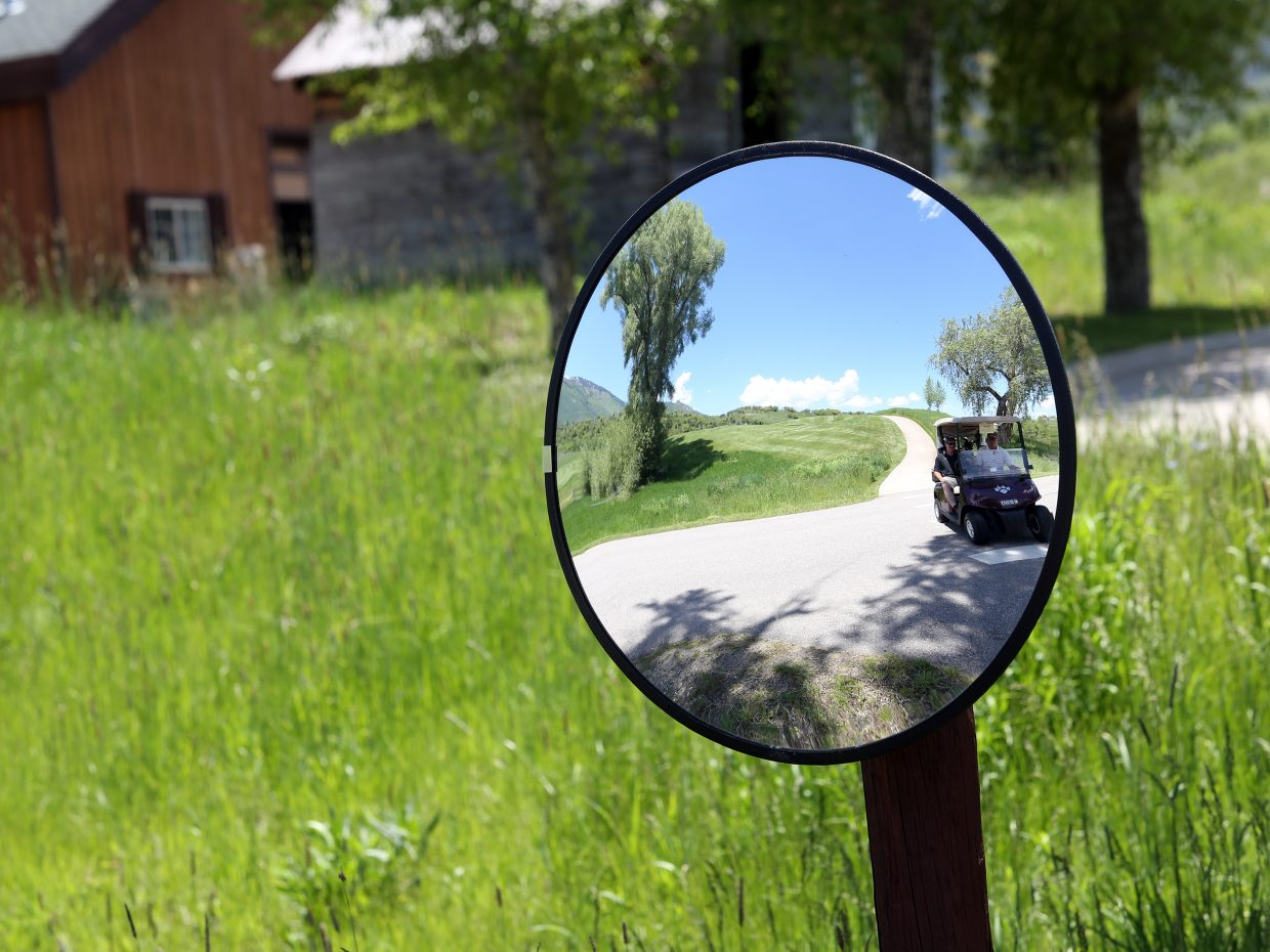 A golf cart is reflected off a mirror near the road between the 18th green and the clubhouse during the 18th annual Ski Town Golf Classic, played Saturday, June 13, 2015, at the Catamount Ranch and Club outside Steamboat Springs.