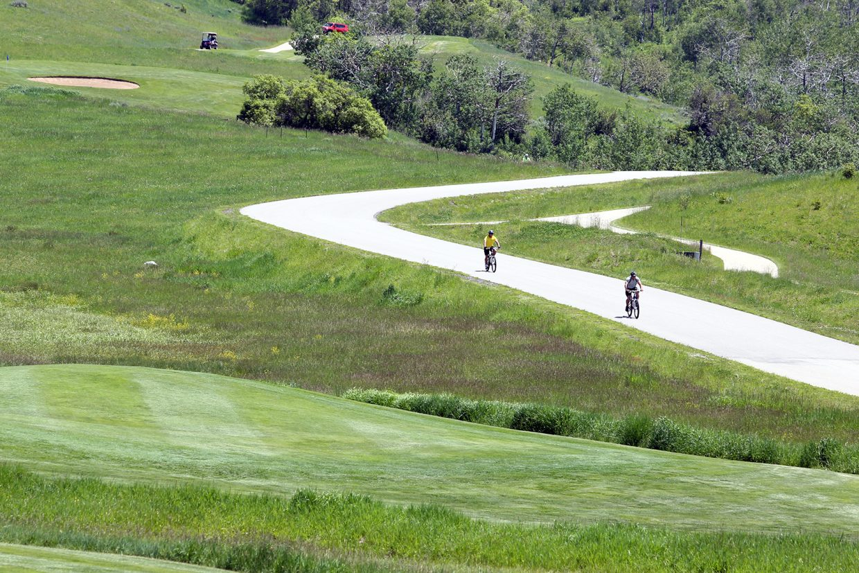 Cyclists ride down the road during the 18th annual Ski Town Golf Classic, played Saturday, June 13, 2015, at the Catamount Ranch and Club outside Steamboat Springs.