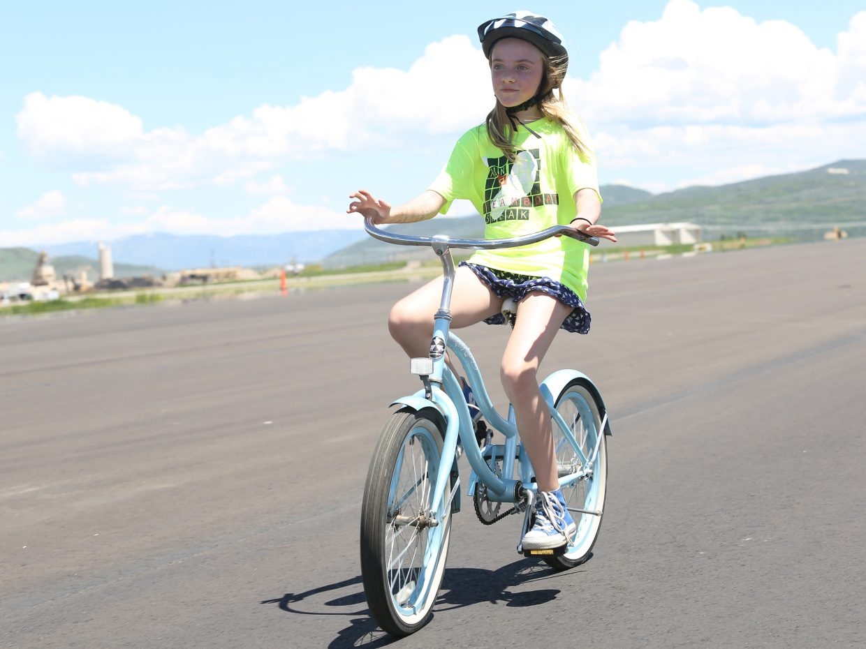 Steamboat Springs resident Avalon Thunstrom, 11, rides her bike down the newly-paved runway Sunday at the Yampa Valley Regional Airport near Hayden. The airport celebrated its grand reopening even though the actual operational opening has been pushed back to June 25.