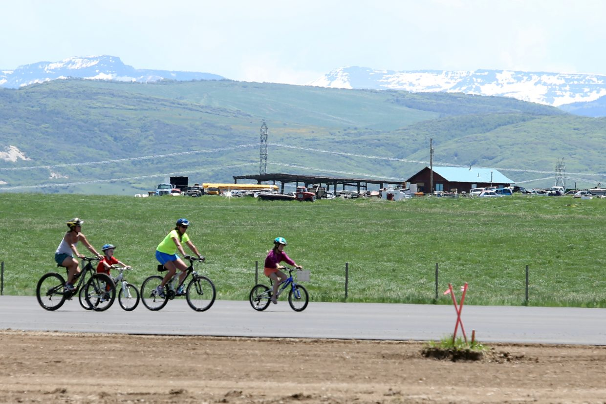 A family rides their bikes down the newly-paved runway Sunday at the Yampa Valley Regional Airport near Hayden. The airport celebrated its grand reopening even though the actual operational opening has been pushed back to June 25.