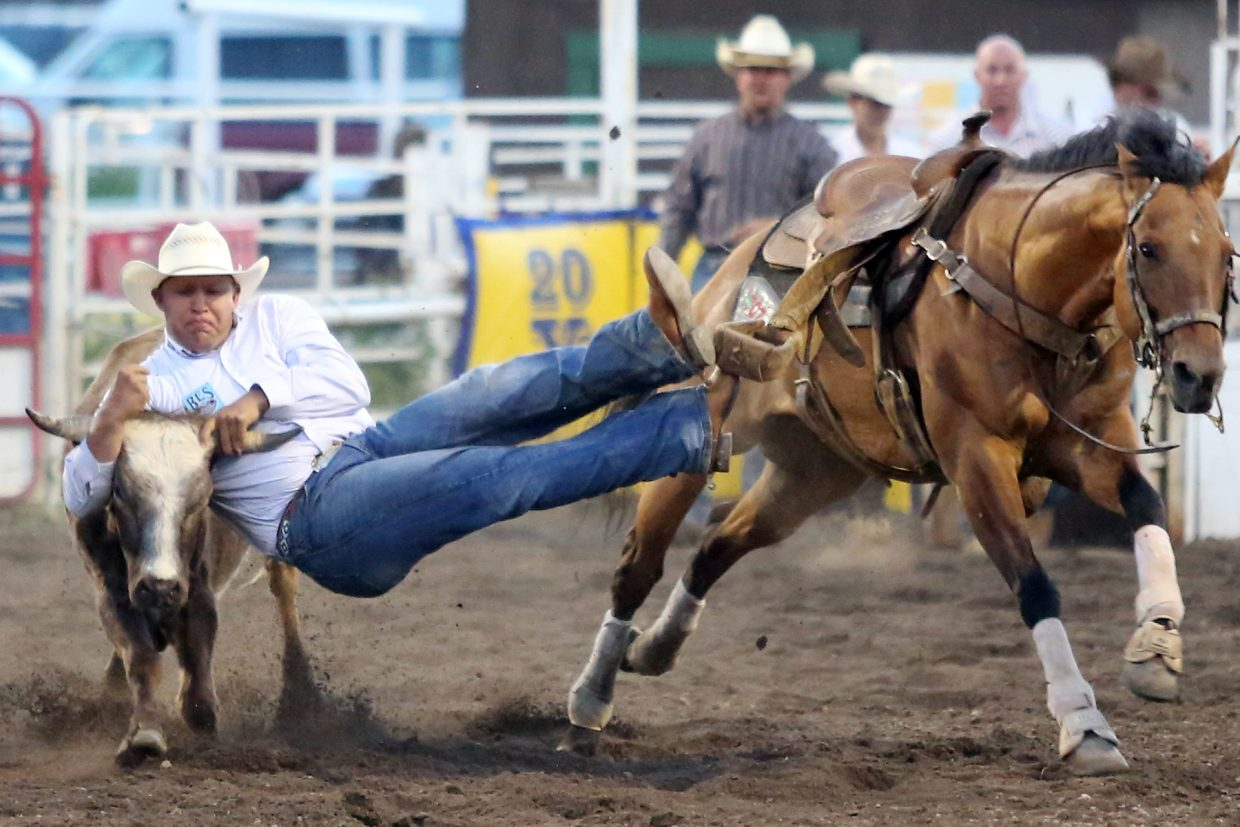 Avery Jamerman, of Riverton, Wyoming, competes in the steer wrestling competition of Friday's season opening Steamboat Springs Pro Rodeo Series at Brent Romick Rodeo Arena in downtown Steamboat Springs.