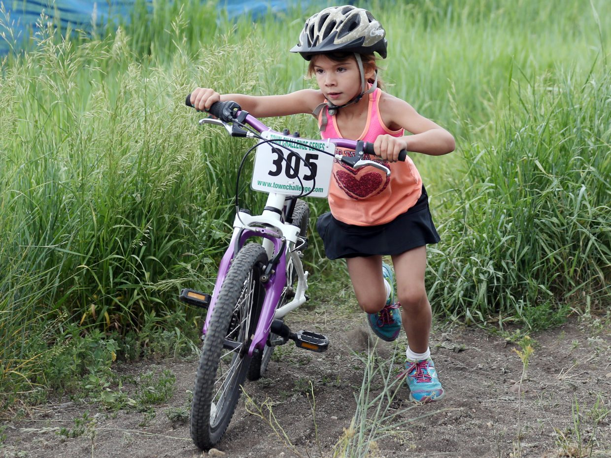Eva Minotto pushes her bike up a hill in the youth coed 7 and 8 division race of the Emerald Envy XC Town Challenge mountain bike race on June 24, 2015, at Emerald Mountain in Steamboat Springs.