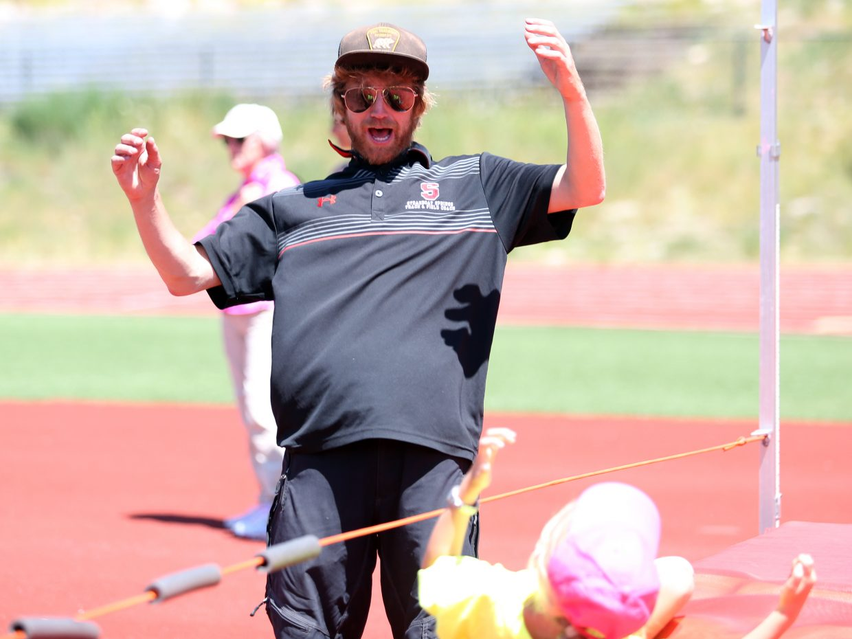 Erik Ramstad, the Steamboat Springs High School cross country coach, reacts to a child attempting the high jump at a youth track and field camp hosted by SSHS on Friday, June 26, 2015, at the school's track. The week long camp ended Friday with a mock track meet.