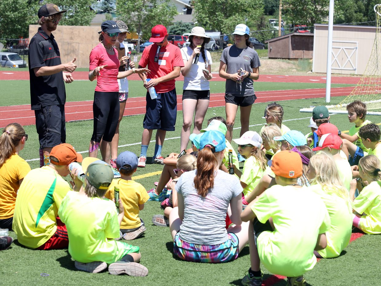 Lisa Renee Tumminello, back left in red, gives children a few parting words at the completion of their youth track and field camp hosted by Steamboat Springs High School on Friday, June 26, 2015, at the SSHS track. The week long camp ended Friday with a mock track meet at the high school.