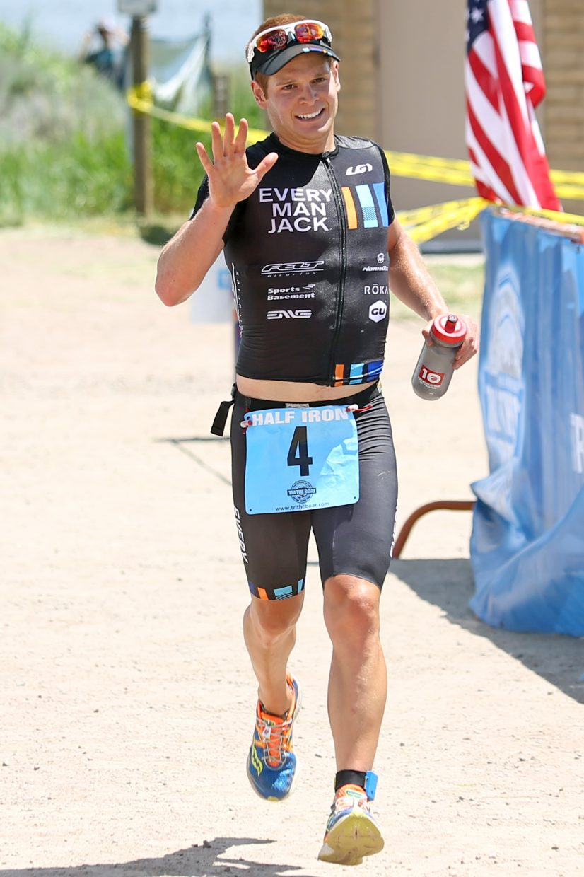 Fort Collins resident Steve Mantell is the first to cross the finish line of the 2015 Tri the Boat half-Ironman triathlon held Sunday, June 28 at Stagecoach State Park.