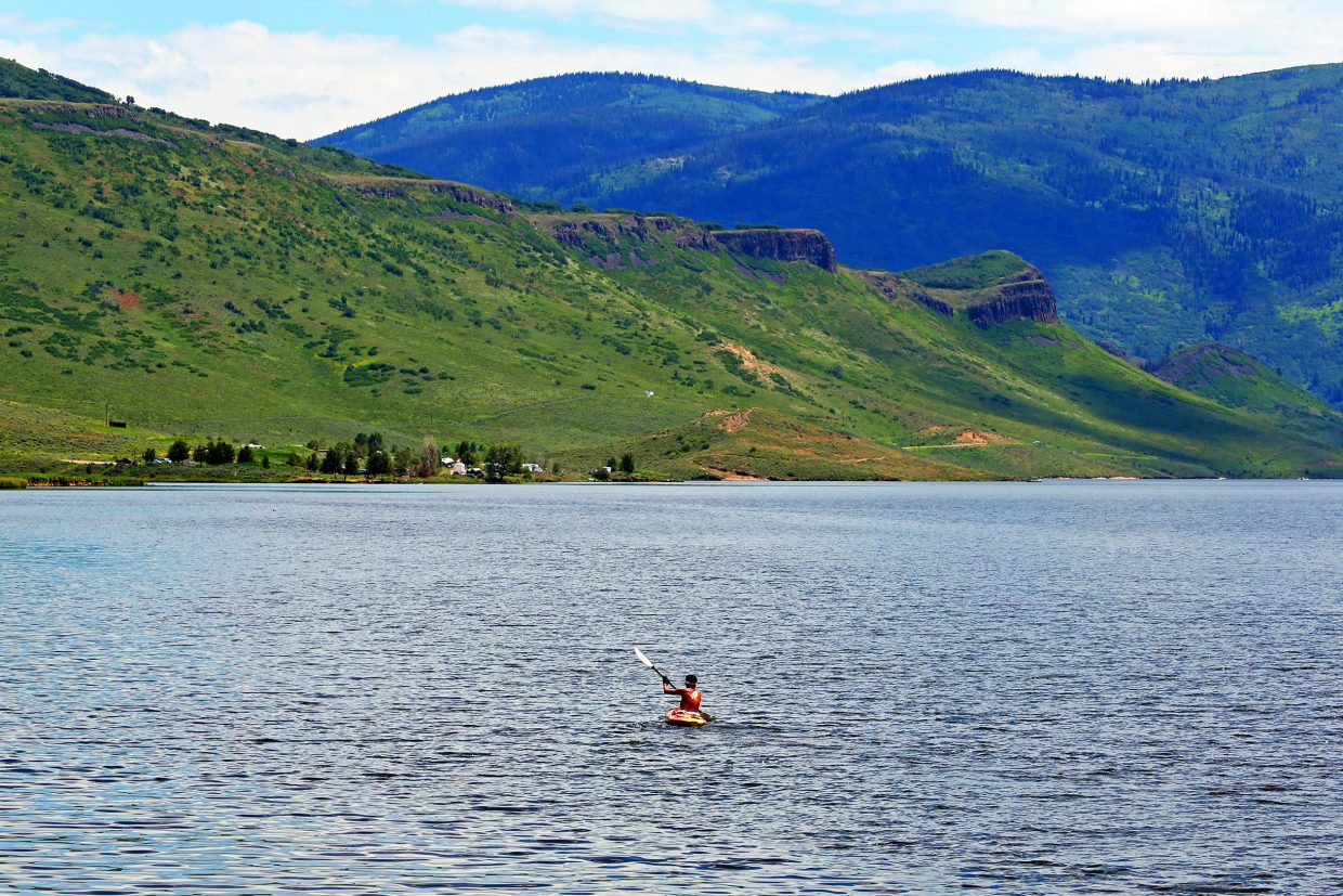 A lone kayaker paddles into the middle of Stagecoach Reservoir on a bright and sunny Sunday afternoon.