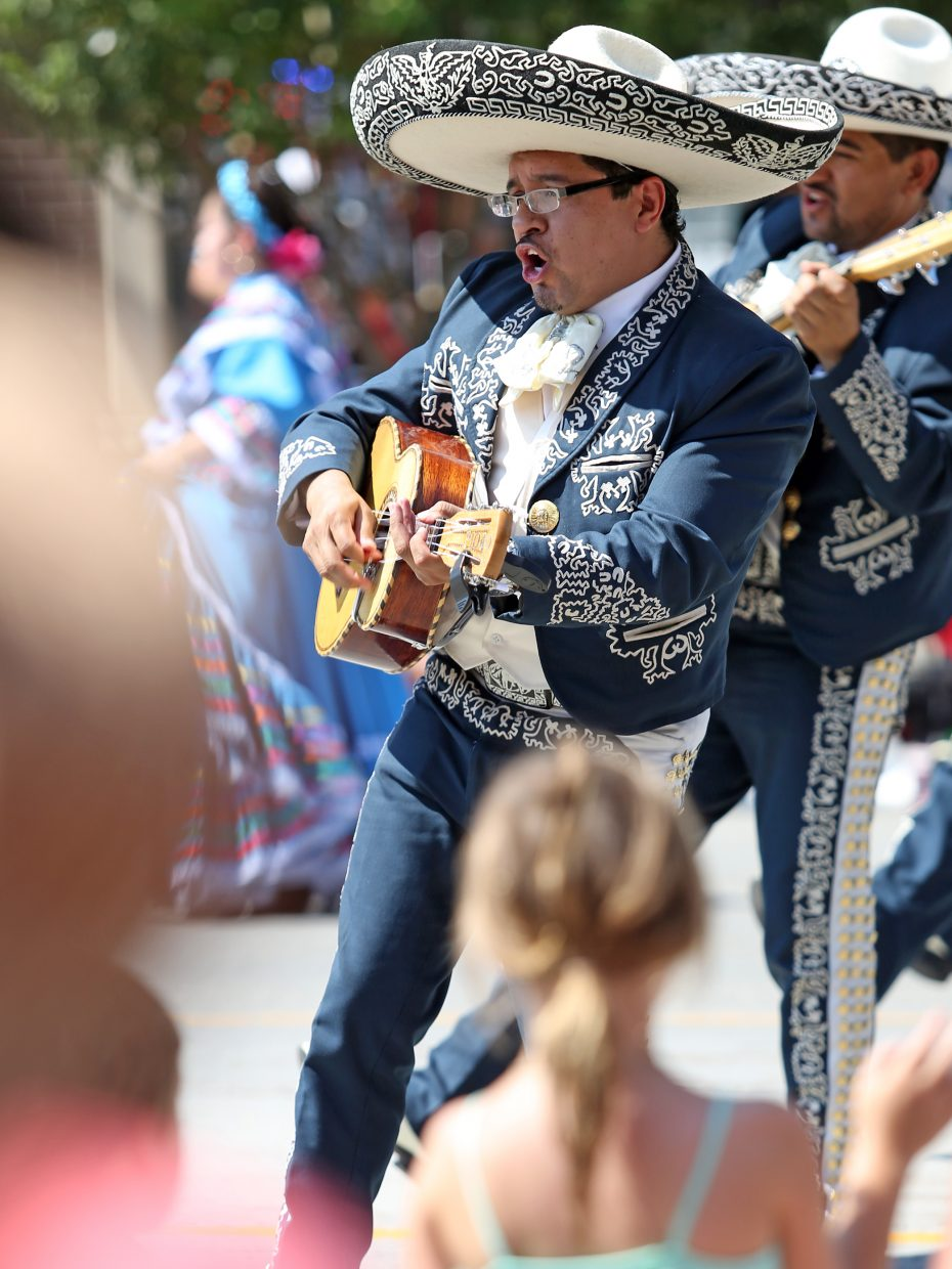 A mariachi player strums his guitar as he serenades the onlookers during Saturday's Fourth of July parade in Steamboat Springs. He was part of a large float entourage for Vaqueros Mexican Restaurant and Taqueria in Steamboat.