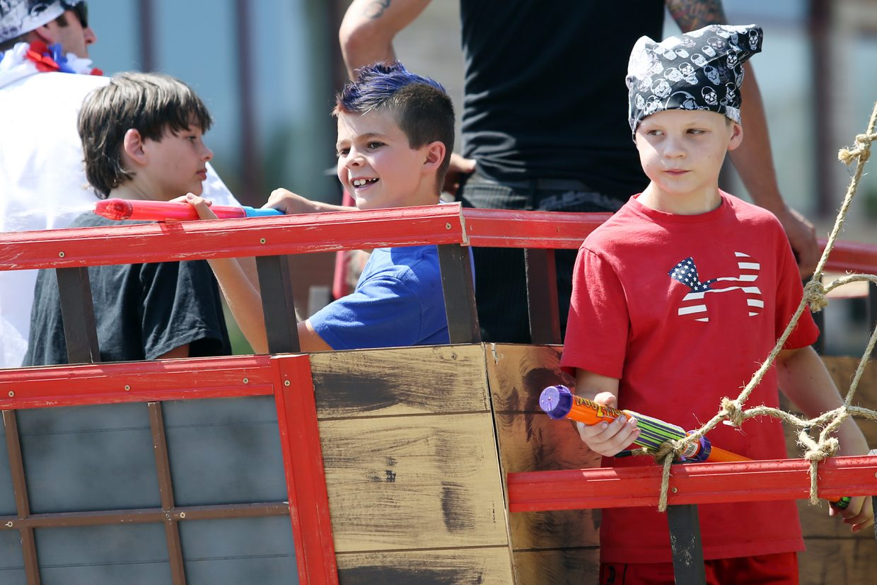 "Boys from the Steamboat Springs Youth Wrestling float spray the crowd with water from their ""pirate ship"" during Saturday's Fourth of July parade in downtown Steamboat."