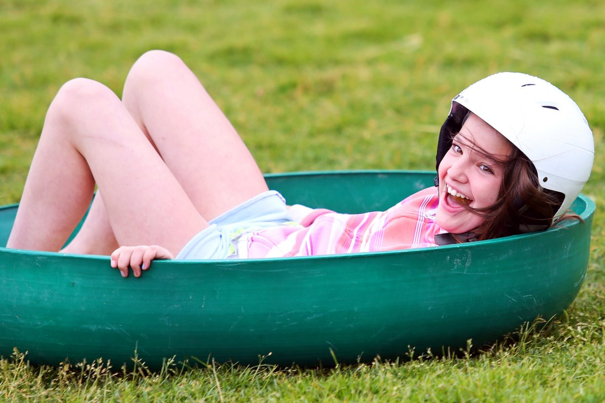 Steamboat Springs resident Liesel Wilkinson, 11, smiles as she reaches the bottom of the Nordic Screamer, the newest summer attraction at Howelsen Hill in Steamboat Springs. The sled ride, which takes you down the ski jumps, opened to the public Sunday.