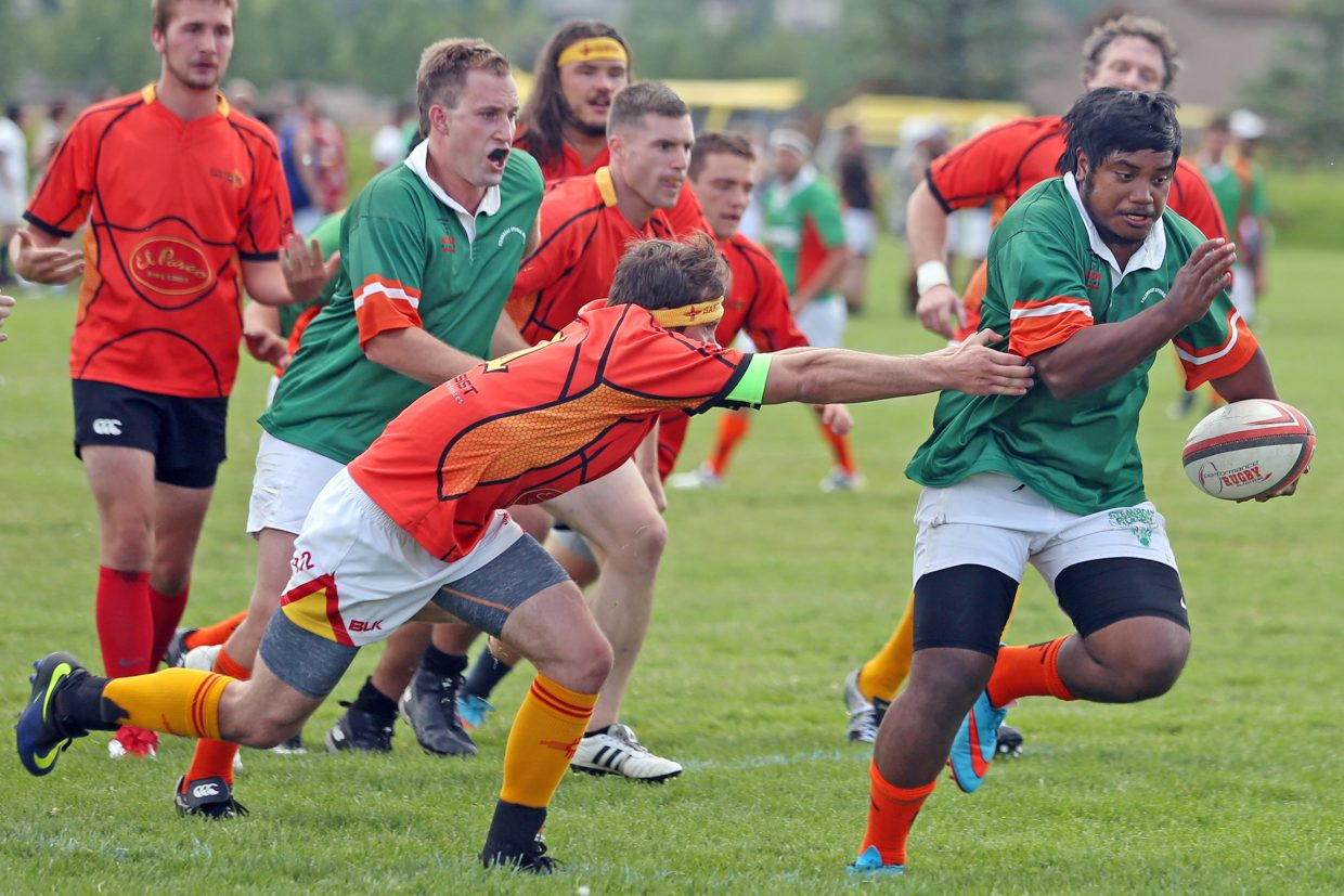 Steamboat RFC's Cantoa Rimon, right, tries to escape the grasp of a New Mexico RFC player during their match on Saturday in the 41st annual Cow Pie Classic at the Ski Town Fields in Steamboat Springs. Steamboat RFC defeated New Mexico, 12-10.