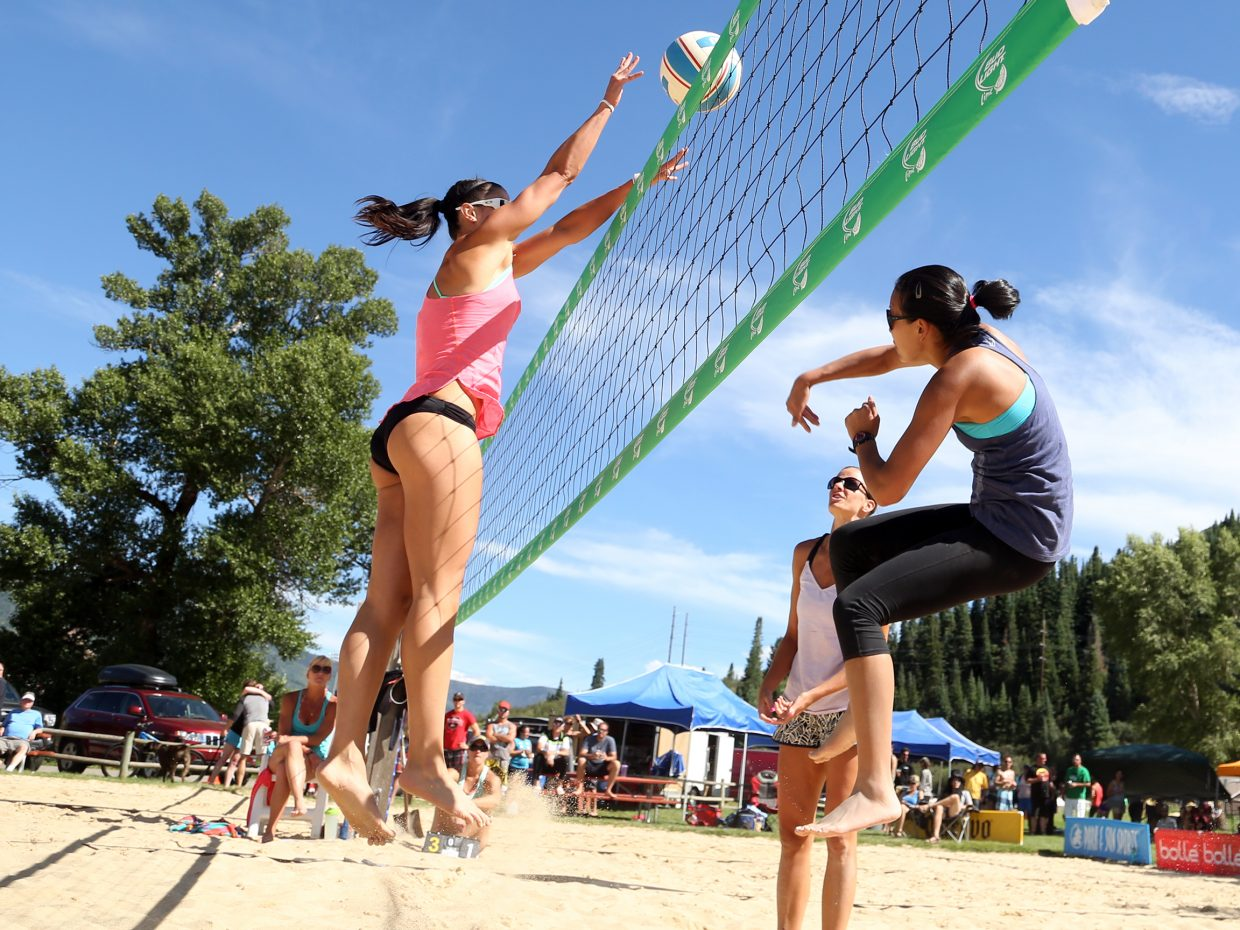 Tess Rogers, left, goes airborne in a block attempt during Sunday's championship match of the women's sand open division of the Steamboat Doubles Volleyball Tournament, played at Howelsen Park. Rogers and teammate Tanya Bond would eventually lose the match to Meghan Barkman (pictured back right) and Christina Shao (far right).
