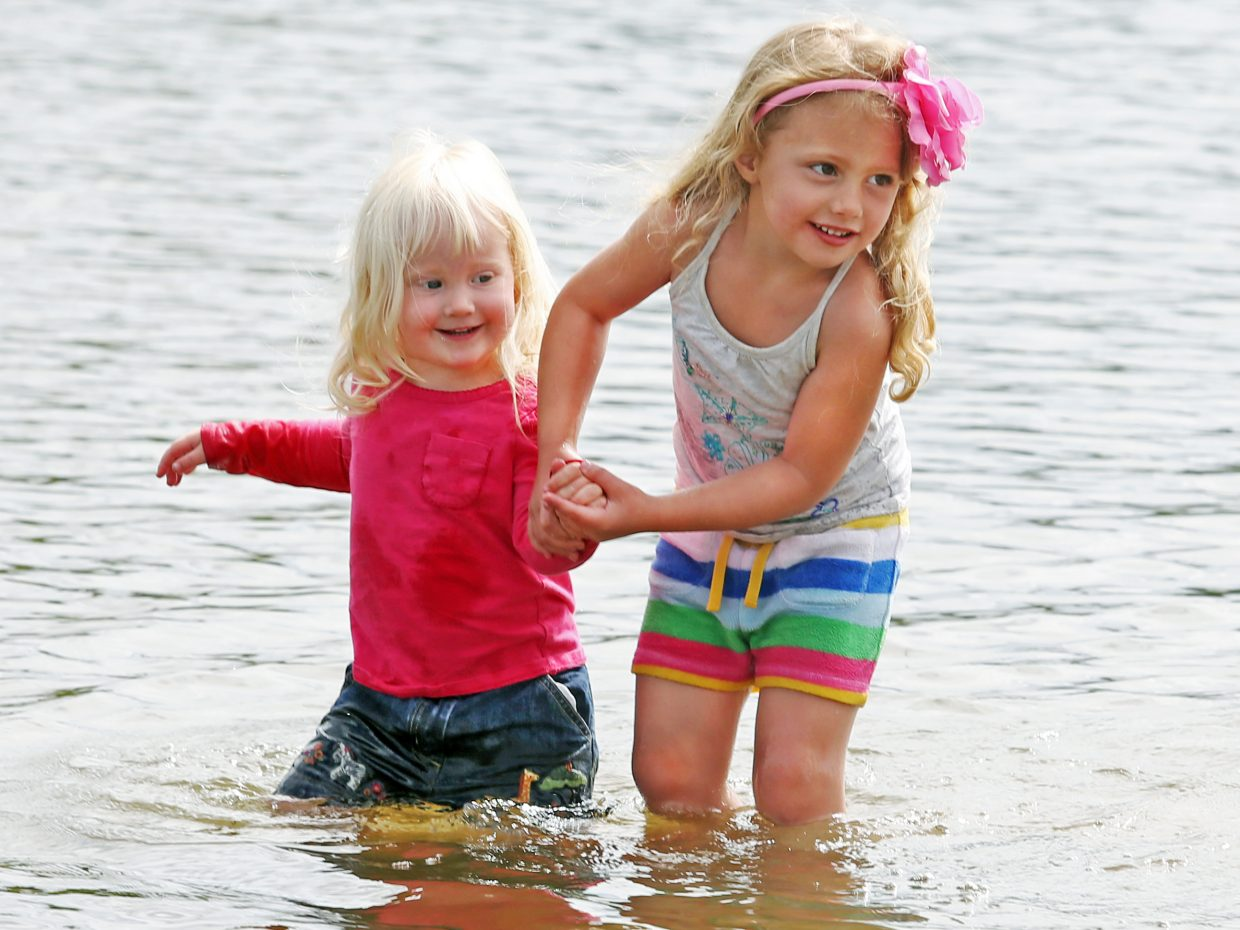 Steamboat Springs resident Josie Dickerson, right, helps her sister Hadley return to the shore of Steamboat Lake on Sunday after the two had been playing in the water. The girls were there watching their mother, Erin Dickerson, compete in the Steamboat Lake Sprint Triathlon.