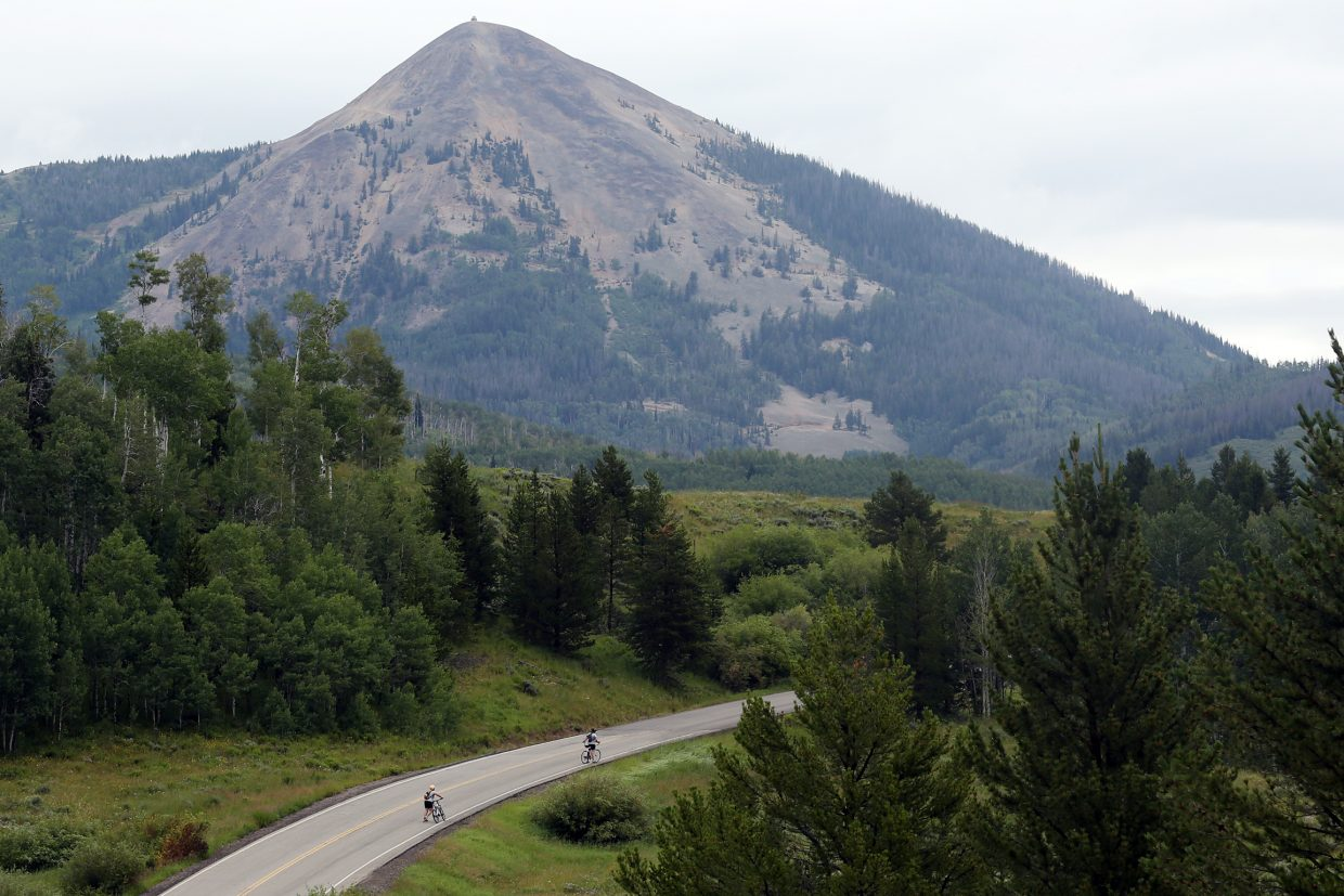 Cyclists climb the road in front of Hahn's Peak during Sunday's Steamboat Lake Sprint Triathlon.