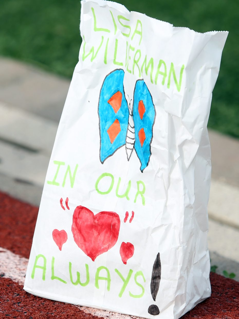 A paper bag dedicated to Lisa Wilderman sits along the track at Steamboat Springs High School Friday during the 2015 Relay for Life event, which raises money for the American Cancer Society. This bag was one of dozens that lined the inside of the track, each dedicated to a different individual.