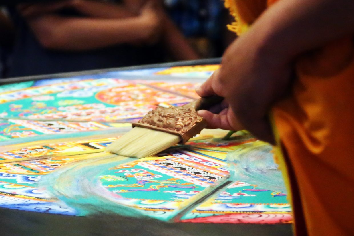 A visiting monk from the Drepung Loseling Monastery begins to brush away the mandala they spent the previous five days making out of sound at the Bud Werner Memorial Library.