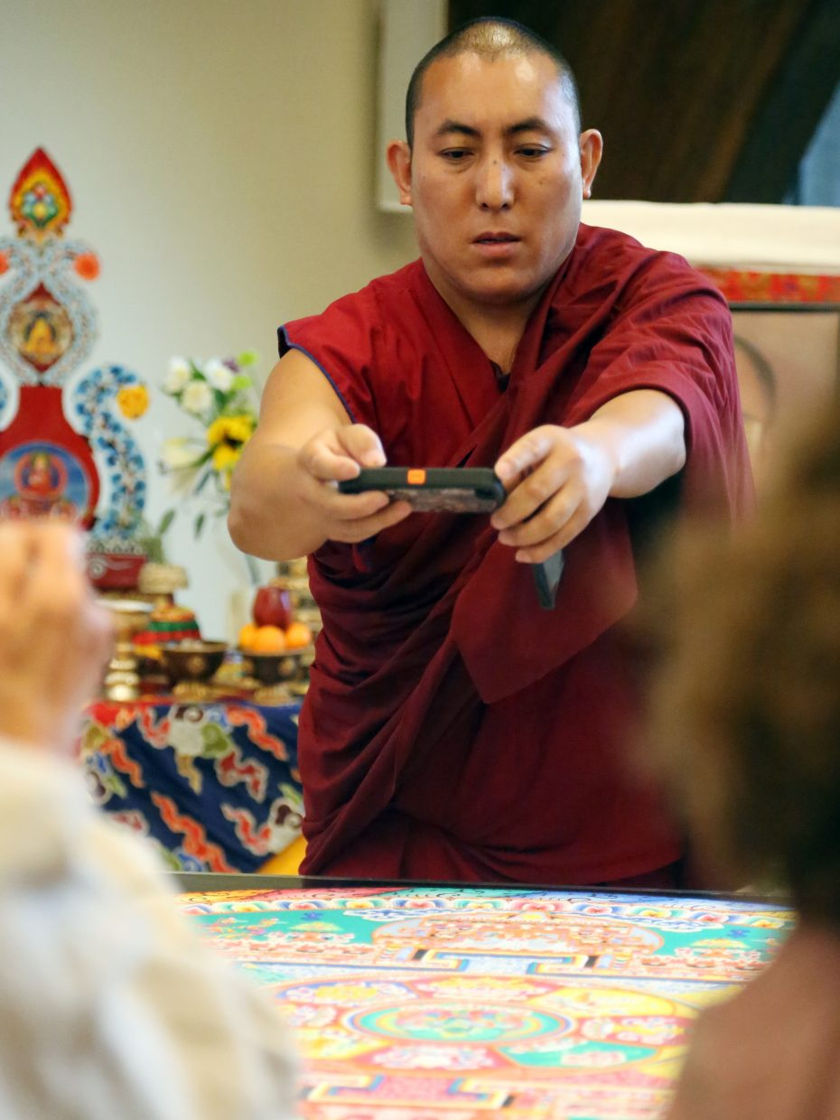 A monk from the visiting Drepung Loseling Monastery takes a picture of the final mandala, made out of colored sand, with a guest's phone on Sunday at Bud Werner Memorial Library in Steamboat Springs.