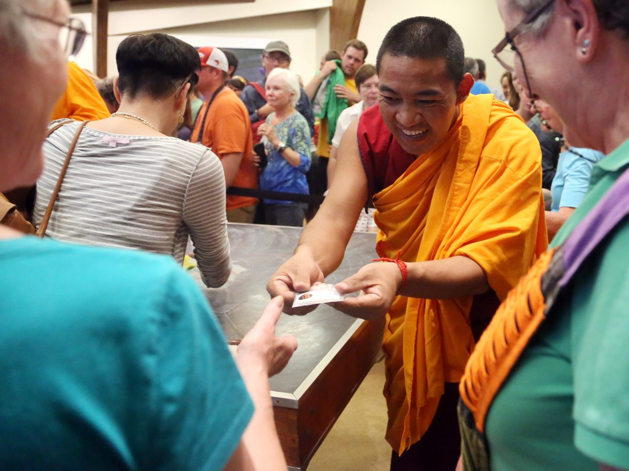 Sand is passed out to guests during the closing ceremony of the visiting Drepung Loseling Monastery monks mandala exhibit on Sunday at the Bud Werner Memorial Library in Steamboat Springs.