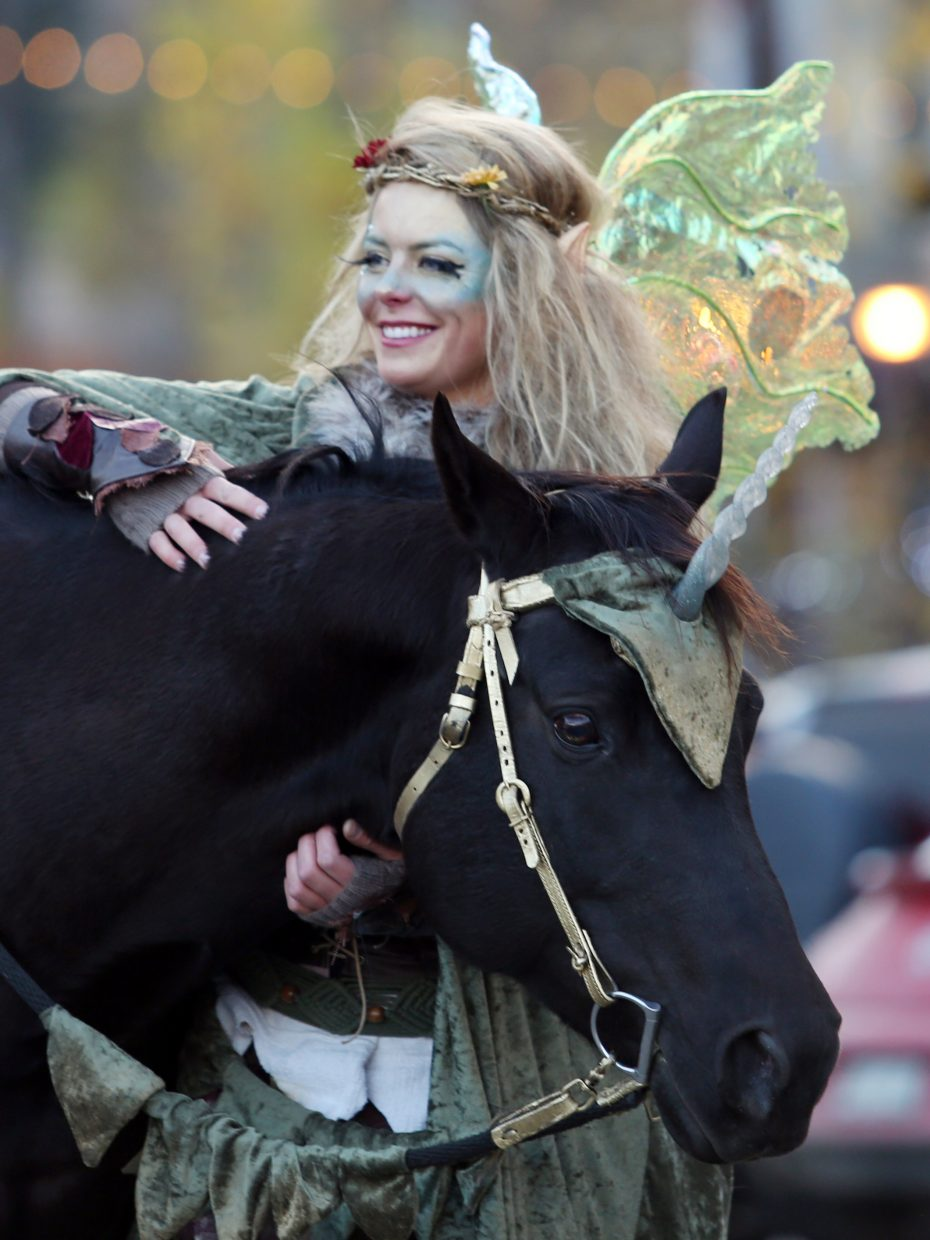 """Tricia Karlson, with her """"unicorn"""" Bane, rode through downtown Steamboat with her sister, Jana Hoffman, similarly dressed, during the Halloween Stroll on Saturday."""