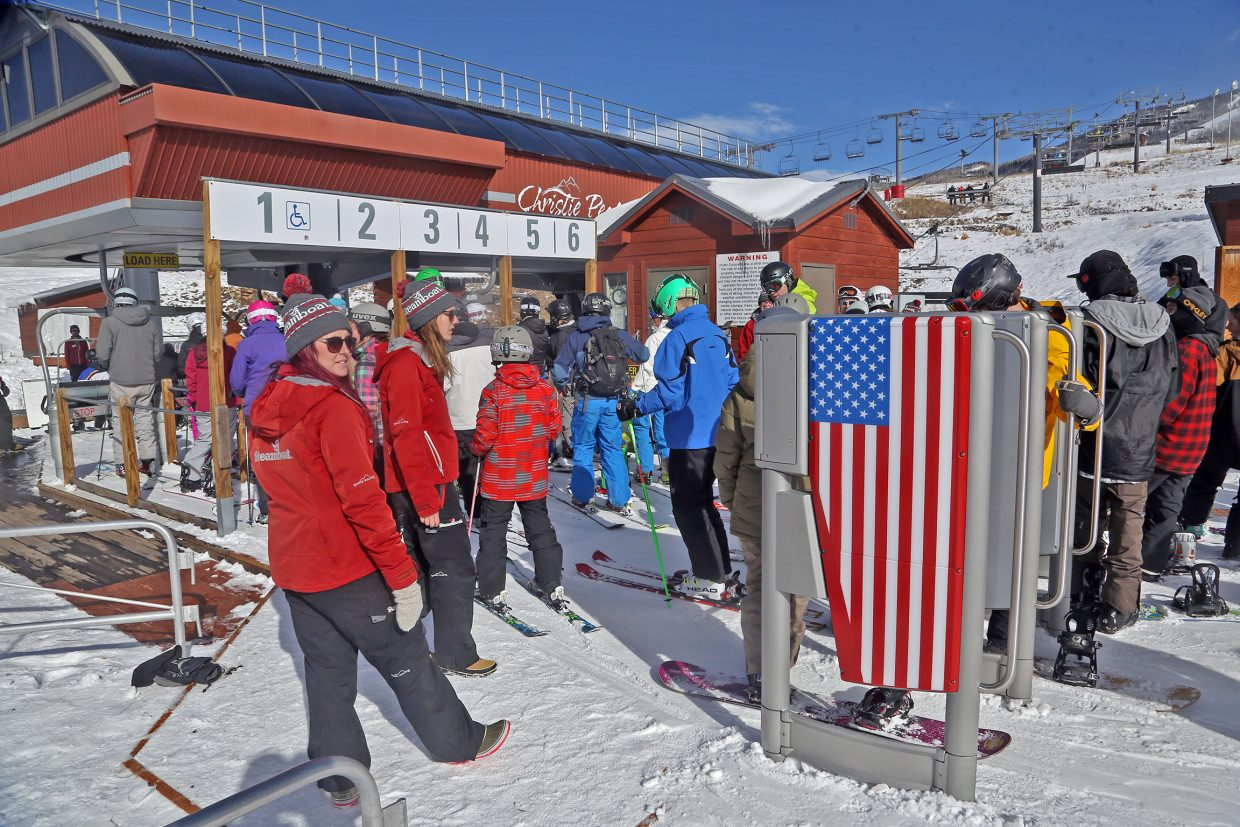 Snowboarders and skiers alike pass through the new RFID gates to gain access to the Christie Peak Express chairlift on Saturday.
