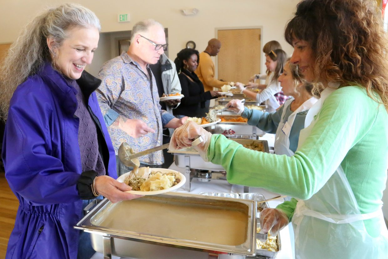 Sarah Snook, right, a United Way volunteer, dishes out gravy to Susan Bell on Thursday during Routt County United Way's community Thanksgiving dinner at the Steamboat Springs community center.