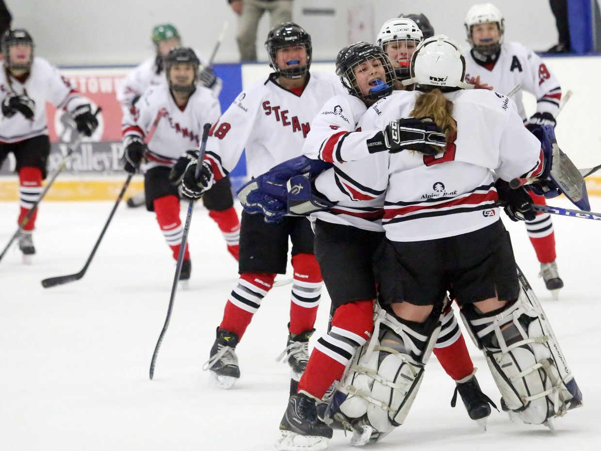 Members of the Steamboat girls' U19 hockey team surround senior goalie Tanner Stover after the team defeated Colorado Select on Sunday to win the Adele Dombrowski tournament inside the Howelsen Ice Arena.