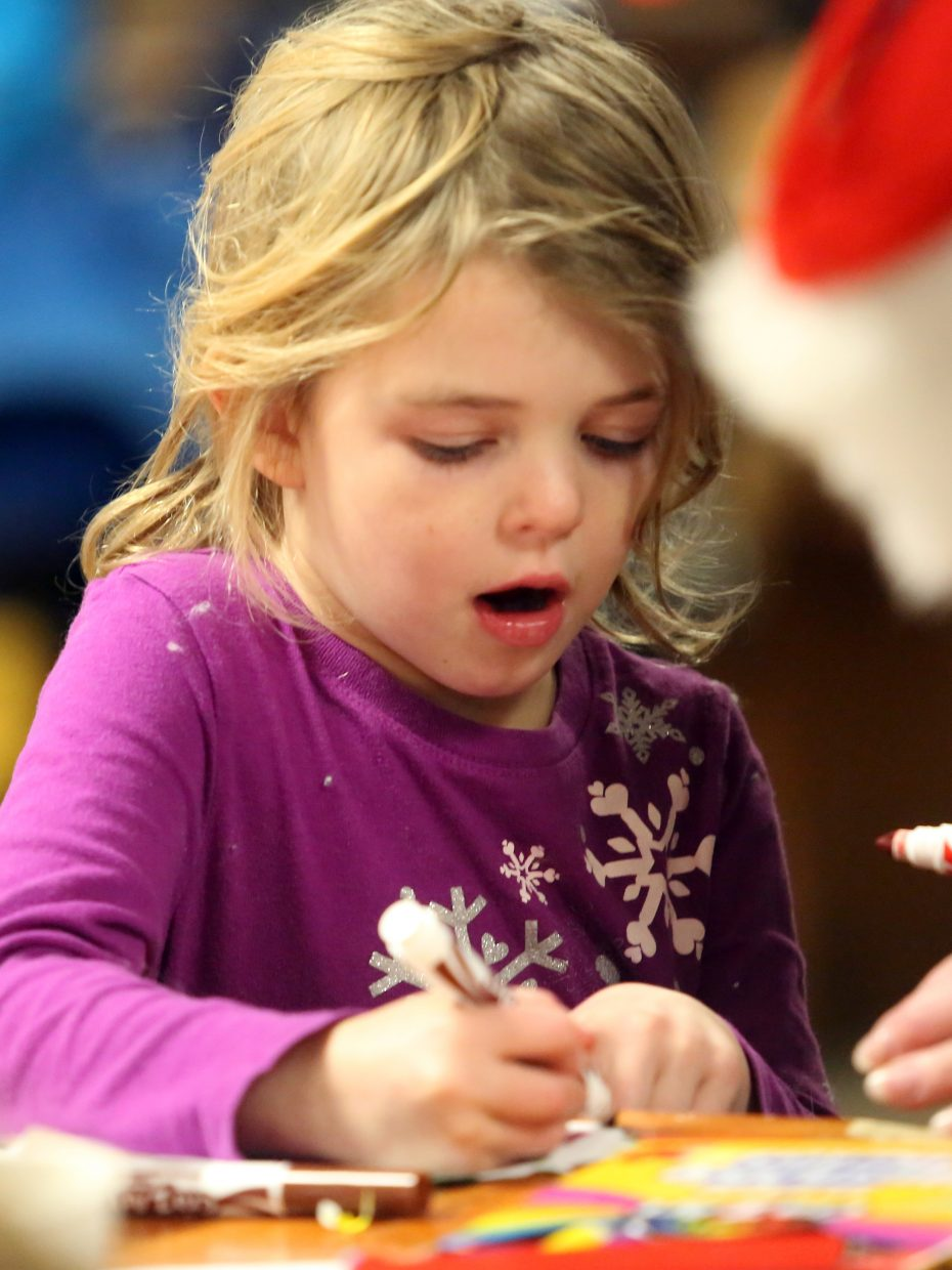 Morgan Gibson, 5, works on her arts and crafts inside the lodge at Howelsen Hill on Sunday.