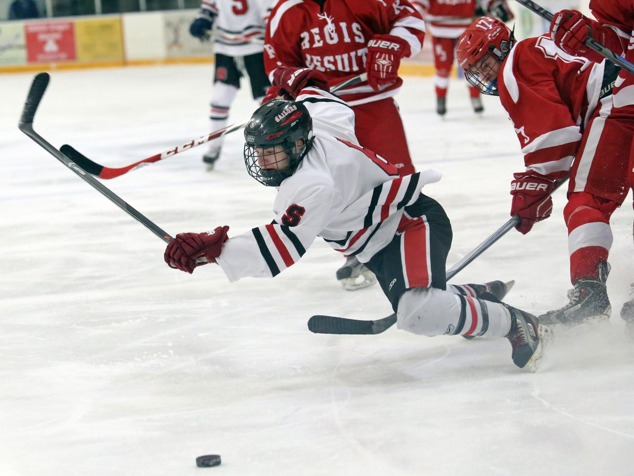 Steamboat Springs senior Brendan Selby is tripped by a Regis Jesuit defender on Saturday at Howelsen Ice Arena. The Raiders won the game, 5-2.