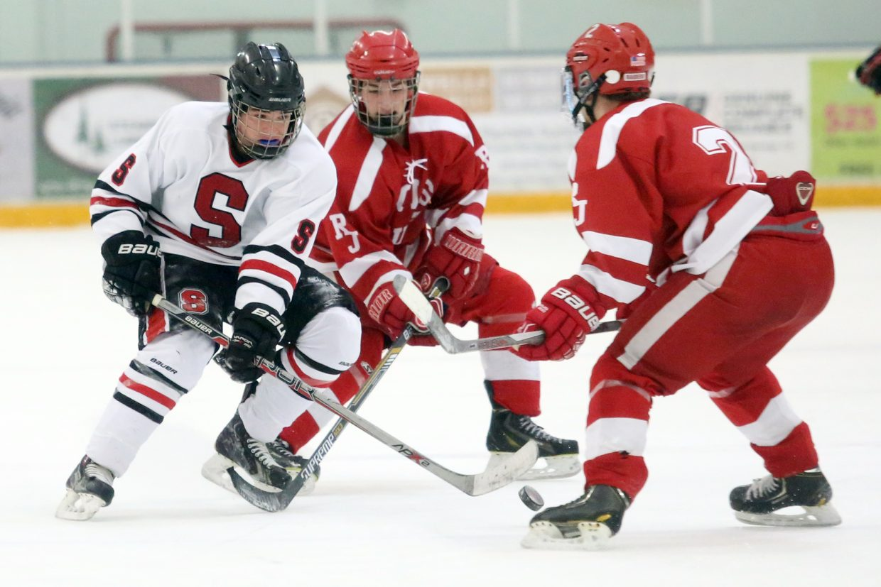 Steamboat Springs freshman Cameron Colombo, left, looks to gain possession of the puck against Regis Jesuit on Saturday at Howelsen Ice Arena.