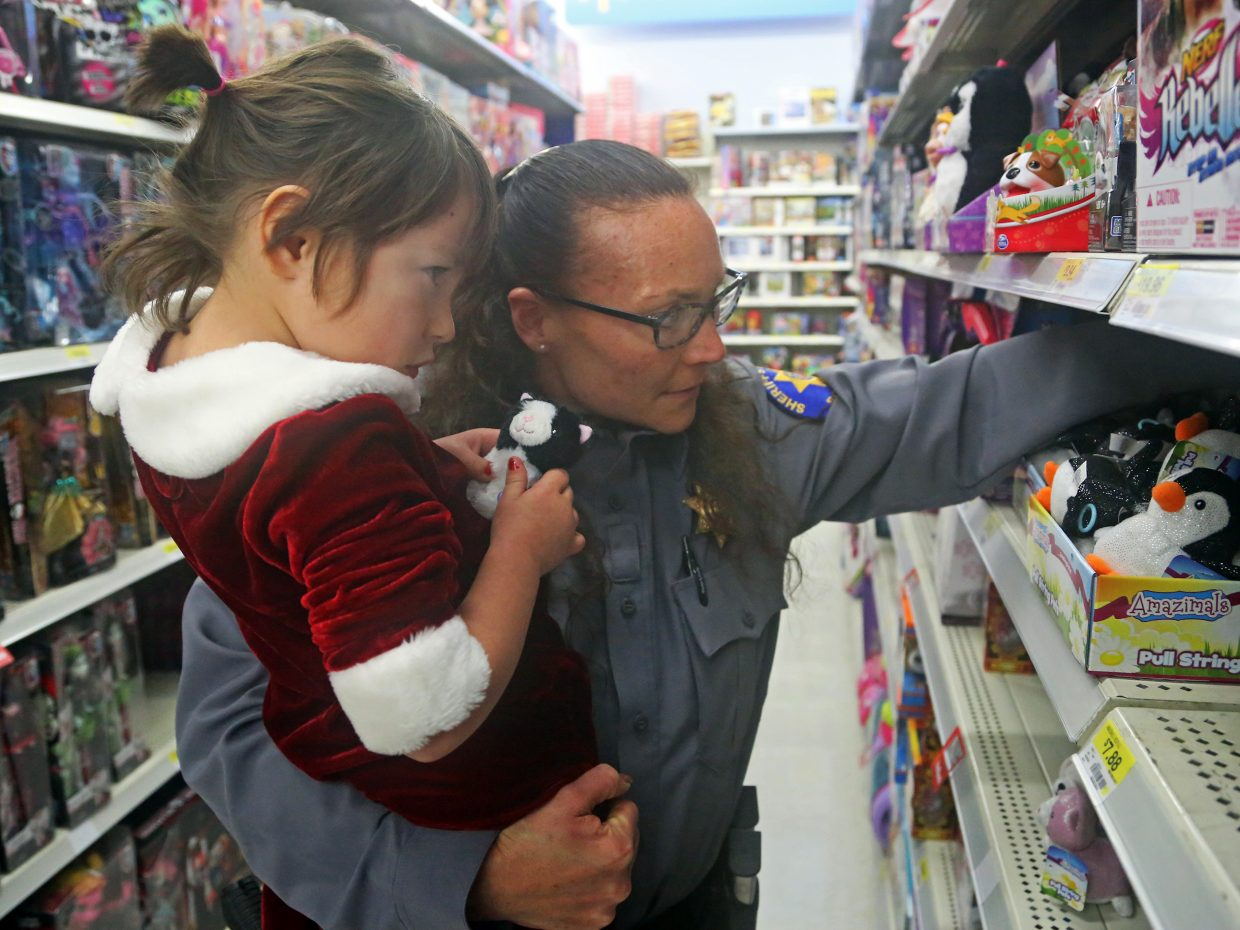 """Lt. Michelle Richardson searches for a stuffed animal with Hayden's Sophia Archuleta, 4, on Sunday at Walmart in Steamboat Springs. Richardson was taking part in the second annual """"Shop with a Cop"""" event, put on by the Routt County Sheriff's Department."""