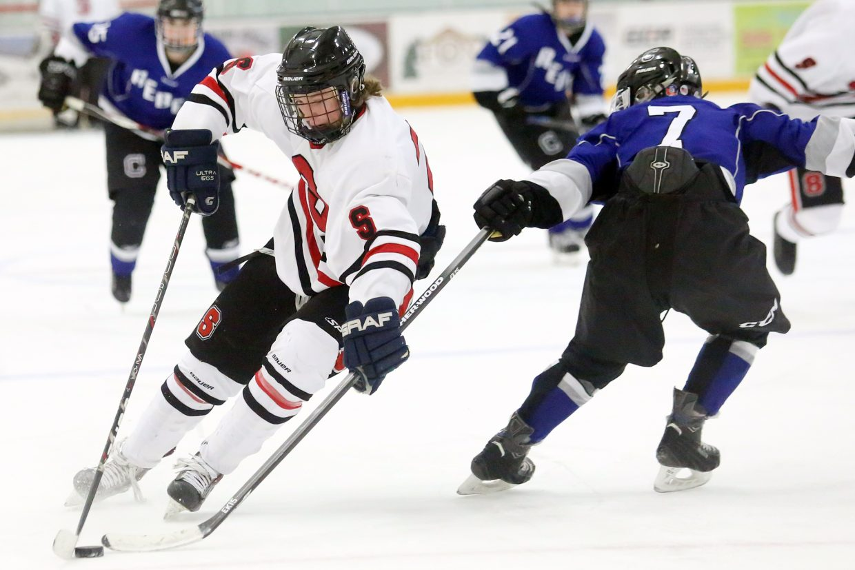 Steamboat Springs senior Bryce Sullivan, left, attempts to pull the stick away from Columbine defender Michael Potter on an offensive attack early in Friday's game at Howelsen Ice Arena. The Sailors won, 6-0.