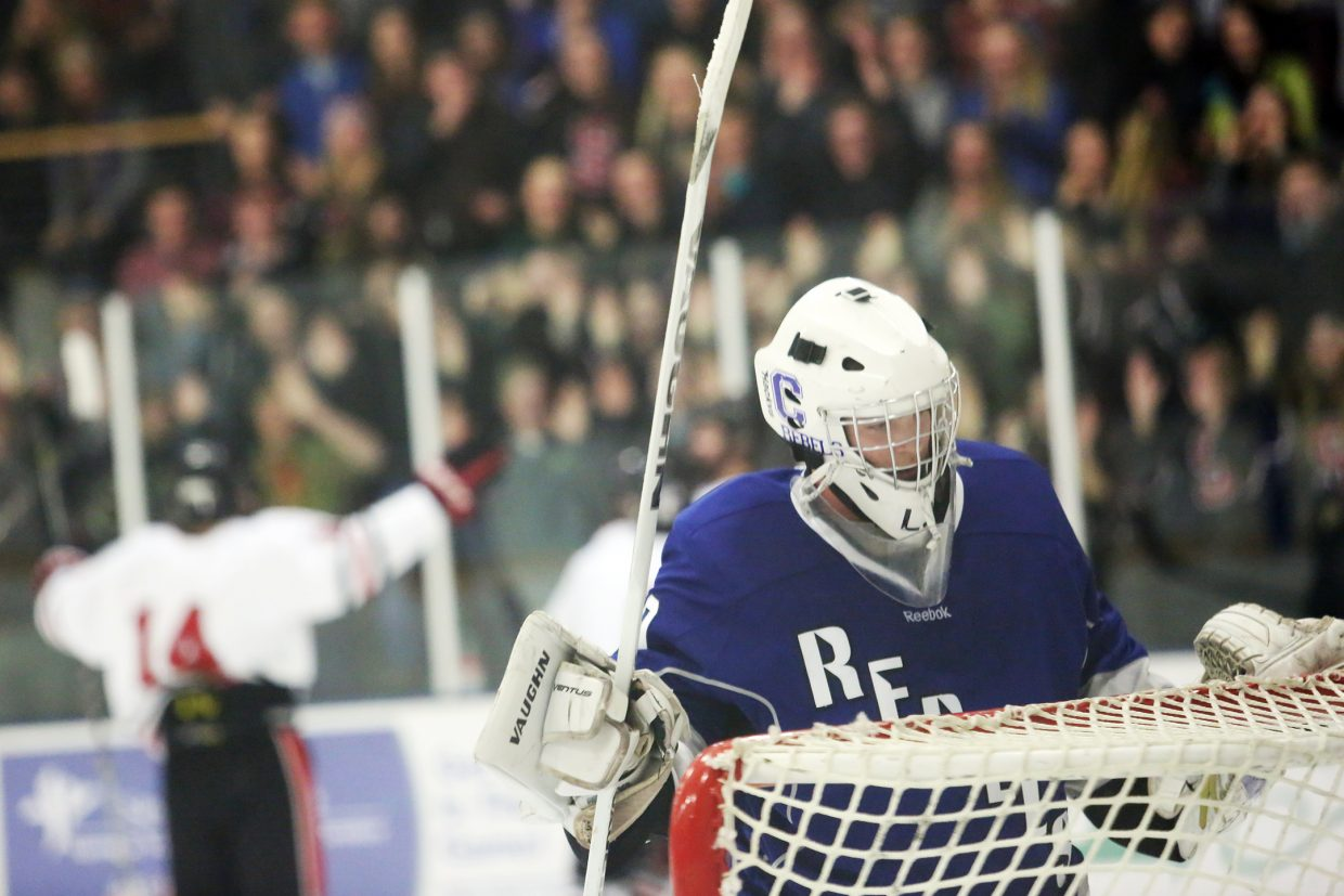 Columbine sophomore goalie L.J. Newell is dejected as the Sailors celebrate in the background after scoring the game's first goal late in the opening period of Friday's game at Howelsen Ice Arena.