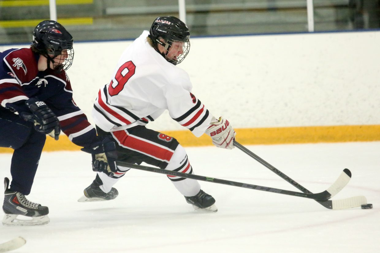 Steamboat Springs senior David Cropper, right, attempts to get past a Dakota Ridge defender on Friday at Howelsen Ice Arena. The Sailors lost 7-1.