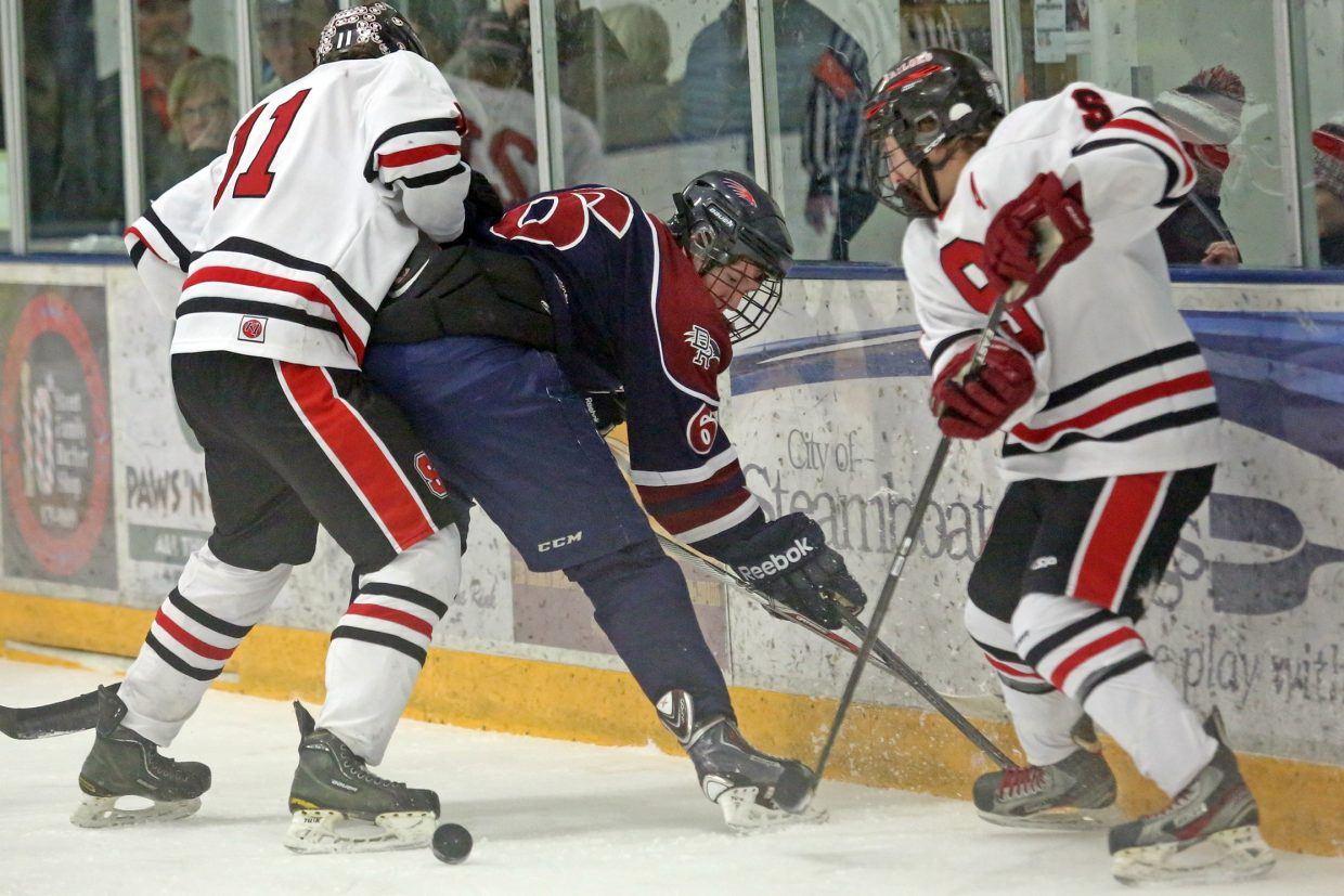 Two Steamboat Springs players surround a Dakota Ridge defender while battling for possession of the puck on Friday at Howelsen Ice Arena.