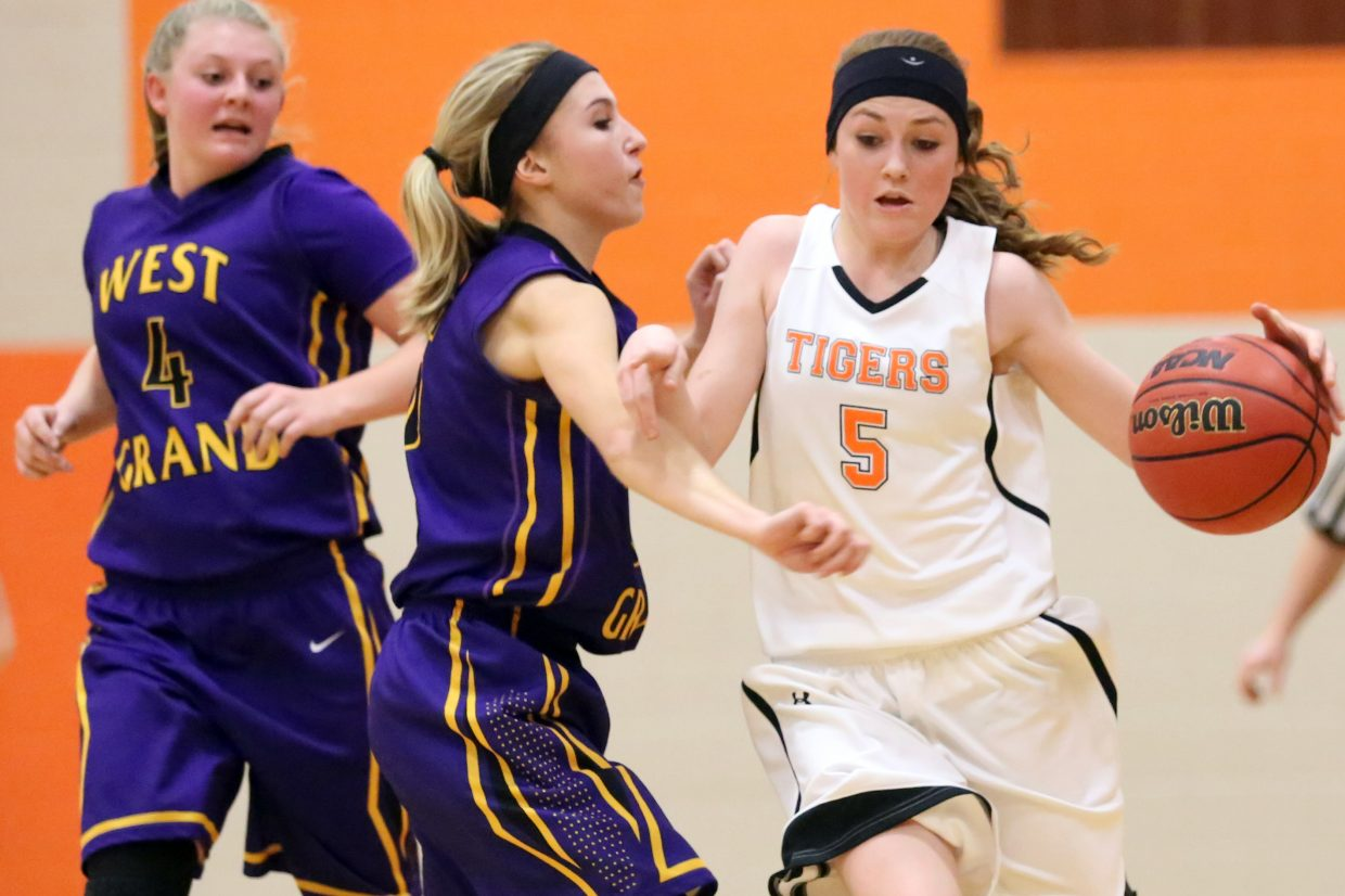 Hayden junior Darian Murphy, right, attempts to dribble around a pair of West Grand defenders in the first half of Friday's game. The Tigers battled, only to fall 51-36.